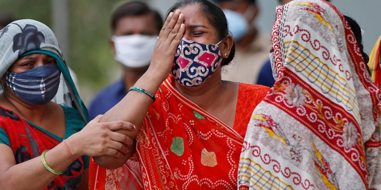A woman mourns after her husband died due to the coronavirus disease (COVID-19) outside a mortuary of a COVID-19 hospital in Ahmedabad, India, May 8, 2021. REUTERS/Amit Dave